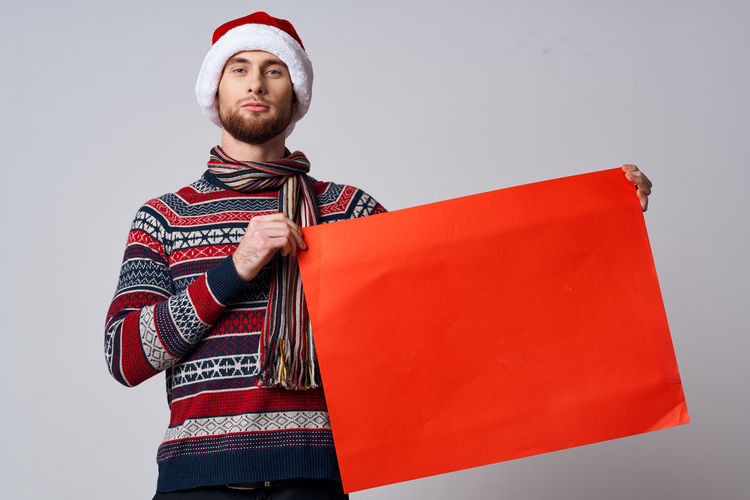 Full length of man standing against red background
