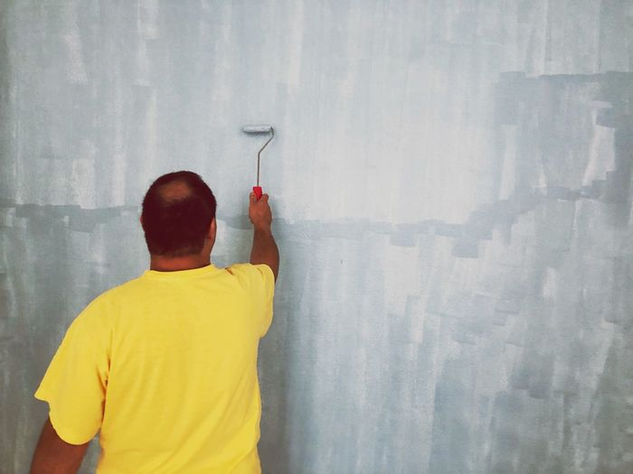 Rear view of man working painting wall