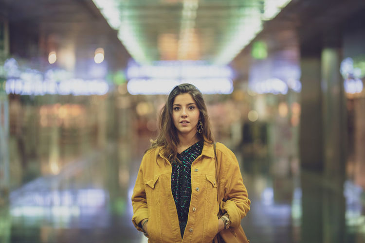 Portrait of young woman standing in corridor of illuminated mall