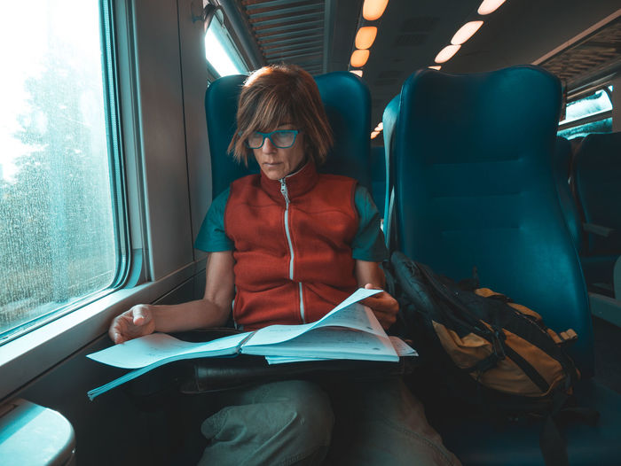 Mature woman reading book while traveling in train