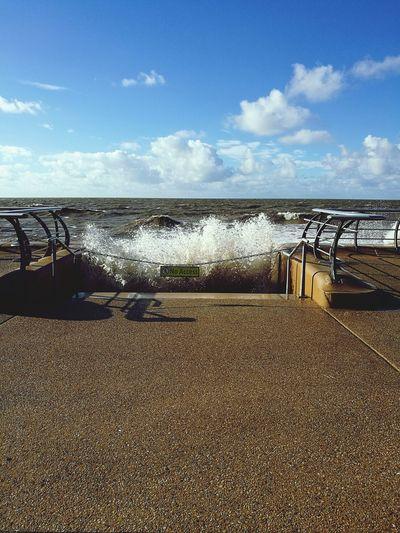 Waves splashing on promenade by sea against sky