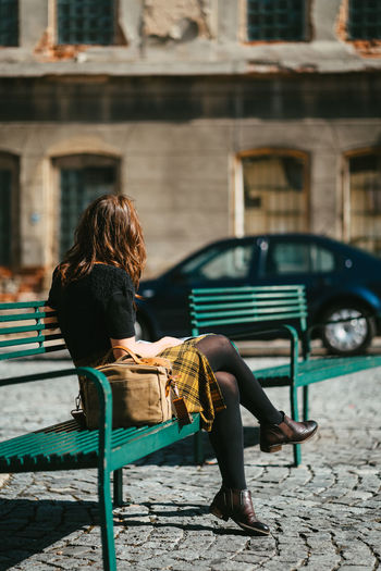 Young european woman in yellow chequered skirt sitting on a green metal bench while social distancin