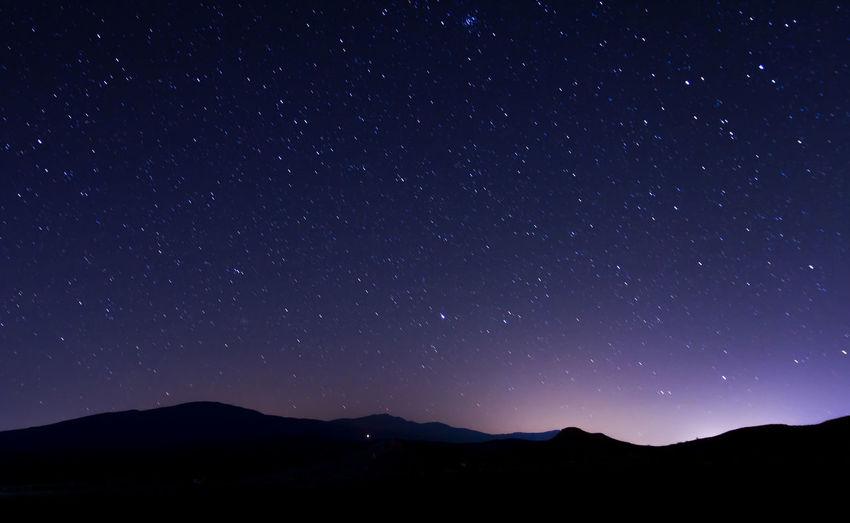 Scenic view of silhouette mountain against star field at night