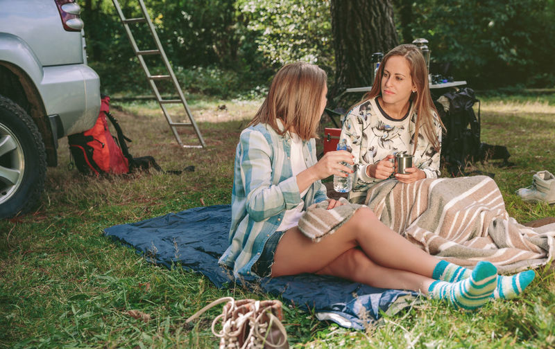 Happy young women friends talking and resting sitting under a blanket in campsite into the forest Camping Campsite Coffee Hiking Horizontal Nature Travel Trip Woman Adventure Backpack Car Caucasian Cup Equipment Female Forest Mountain Off Road Outdoors Sleeping Bag Tent Two People Vehicle Young Adult