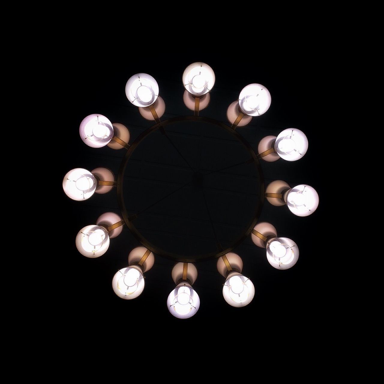 Directly Below Shot Of Illuminated Light Bulbs Against Black Background