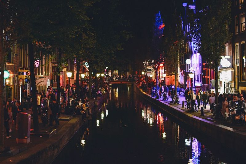 EyeEm Best Shots EyeEmNewHere EyeEm Gallery Amsterdam Illuminated Night Architecture Building Exterior Built Structure City Water Group Of People Reflection Large Group Of People Crowd Nature Real People Building Tree Incidental People Canal Plant Street Outdoors