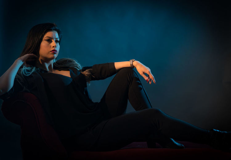 Woman looking away while sitting against wall