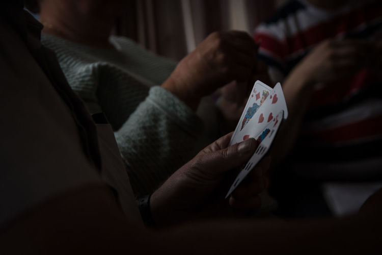 Midsection of people playing cards at home