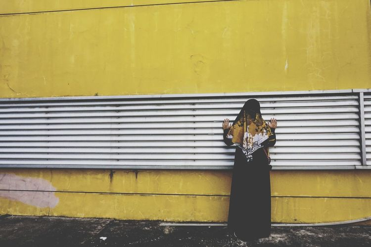 Rear view of woman standing by yellow wall