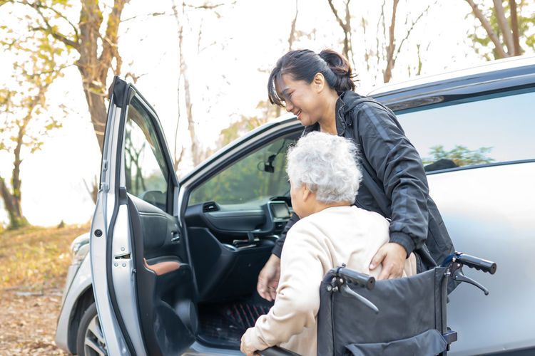 Smiling woman assisting senior woman sitting in car