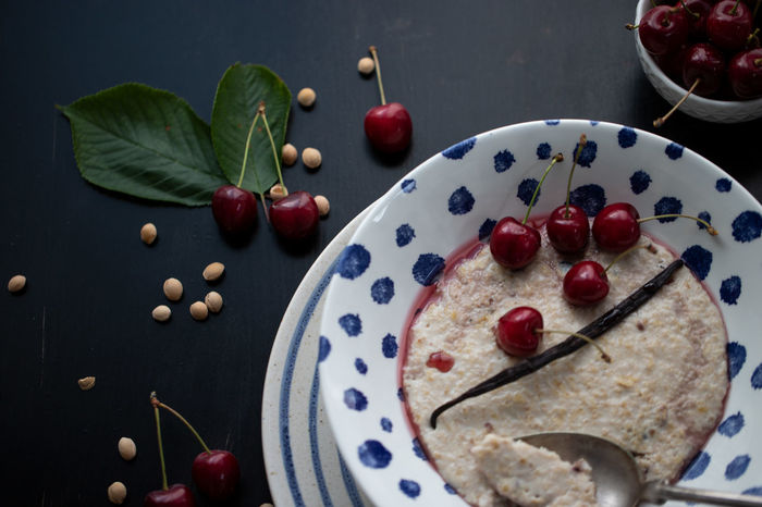 Fresh homemade Porridge with cherries Black Background Breakfast Cherries Freshness Homemade Porridge Vanilla Bean Berry Fruit Cherry Close-up Delicious Food Food And Drink Freshness Healthy Eating Indoors  Leaf Moody Porridge Bowl Ready-to-eat Red Still Life Table Tasty Vanilla