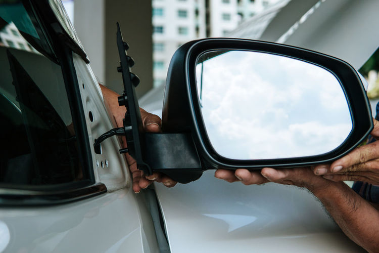 Reflection of man on side-view mirror of car