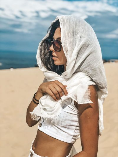 Young woman wearing sunglasses standing at beach