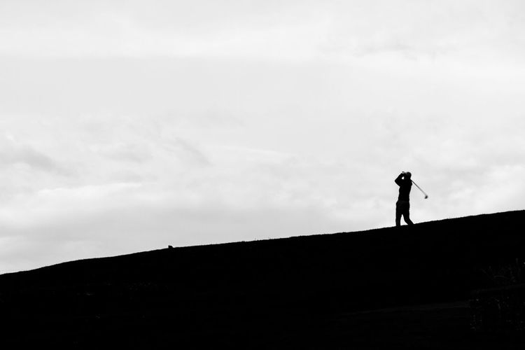 Silhouette of a golfer in action Action Shot  Black And White Contrast Day Full Length Golf Golfer Golfers Swing Hill Landscape Leisure Activity Lifestyles Nature Outdoors Outline Scenics Silhouette Sky Sport Standing Tranquil Scene Tranquility