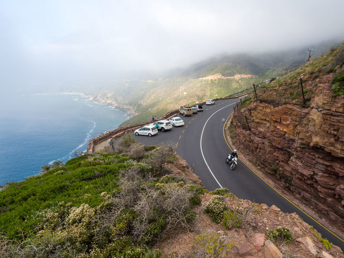High Angle View Of Cars On Road By Sea Against Sky