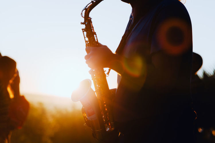 Man playing a saxophone at sunset with an orange sun hiding behind the hill in the background. Analogue Sound Saxophone Man Sunset Music Concert Jazz Sound Orange Color Playing Saxophone Debod´s Temple Viewpoint Debod West Park Madrid SPAIN Chill Chillout Analogue Music Live Music Streetwise Photography