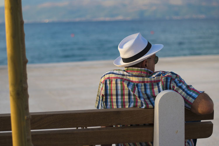 Old Man Beauty In Nature Casual Clothing Day Hat Leisure Activity Lifestyles Nature Old Man And The Sea Old Man Sitting One Person Outdoors Real People Rear View Relaxation Scenics Sea Sitting Sun Hat Vacations Water