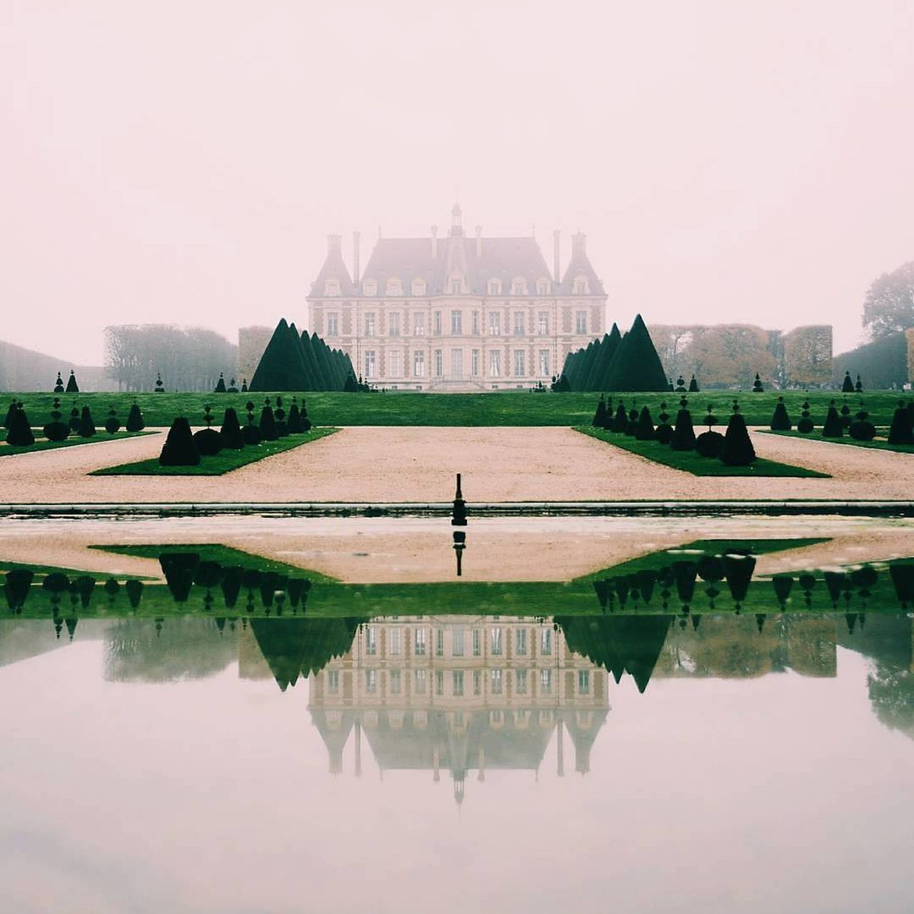 Castle Reflecting On Pond Against Sky During Foggy Weather