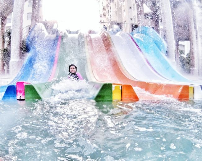 Fun Water Leisure Activity Enjoyment Swimming Pool Splashing Water Slide Vacations One Person Motion People Excitement Water Park Lifestyles Smiling Cheerful Happiness Day Outdoors