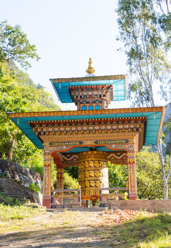 ASIA Travel Architecture Belief Bhutan Buddhism Building Building Exterior Built Structure Day Nature No People Ornate Outdoors Place Of Worship Plant Prayer Wheel Religion Roof Shrine Sky Spirituality Tourism Tree
