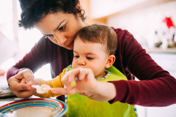 Mother & Daughter Motherhood Eating Healthy Eating Lifestyles Togetherness Family With One Child Childhood Child Family Bonding Parent Females Indoors  Women Holding Love Mother Innocence Care Positive Emotion Son Daughter Headshot Focus On Foreground