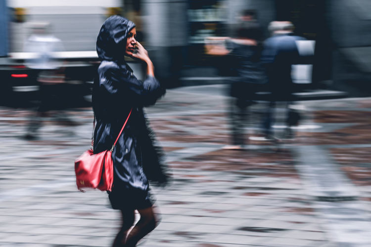 Blurred Motion Of Woman Walking On City Street During Rainy Season