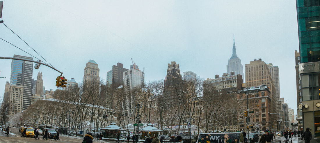 Architecture Bryant Park NYC Building Exterior Built Structure City City Life Cityscape Clock Tower Cold Temperature Day Empire State Building Large Group Of People Outdoors People Sky Skyscraper Snow Snowing Travel Travel Destinations Tree Urban Skyline Winter