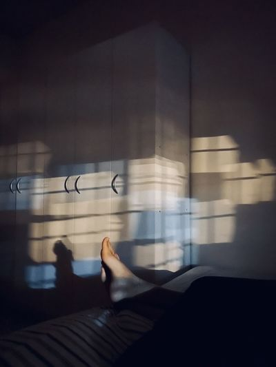 Low section of person with shadow on window