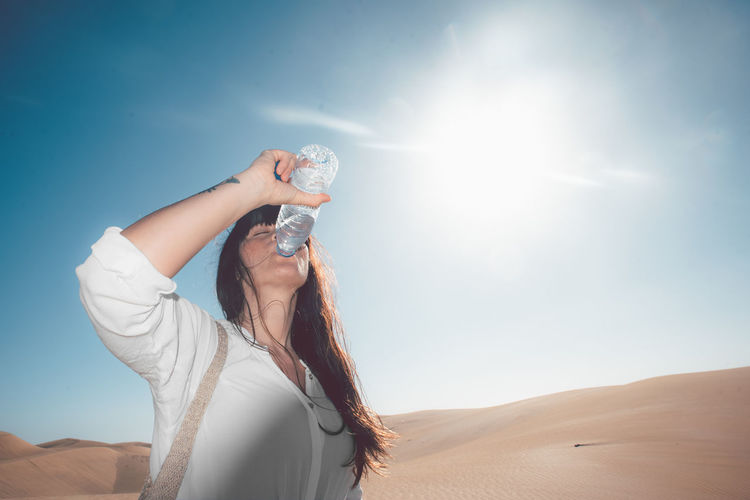 Low angle view of mid adult woman drinking water while standing at desert against sky during sunny day