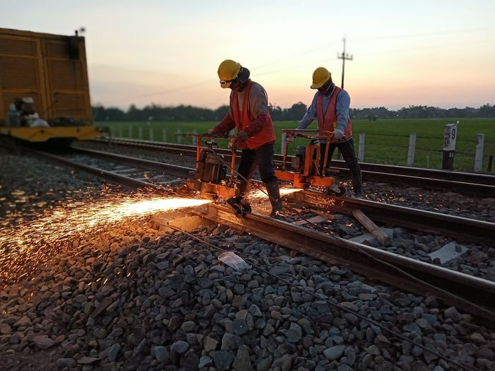 People working on railroad tracks against sky during sunset