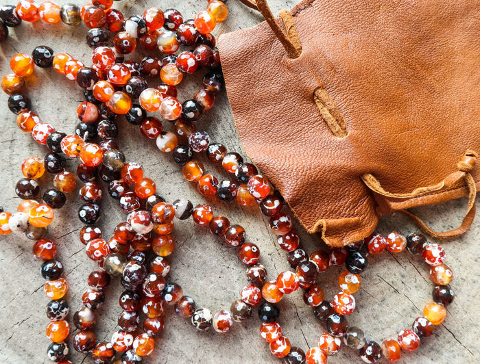 Sunny beads of amber fireplace faceted agate with leather jewelry pouch bag on rustic background Orange Color No People Close-up High Angle View Bead Directly Above Still Life Indoors  Table Full Frame Red Jewelry Temptation Luxury Personal Accessory Beads Sunny Faceted Crystal Ball Agate Stone Leather Pouch Bag Rustic Style Gift Holiday