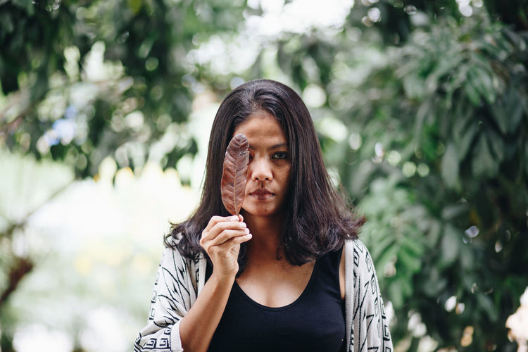 Mid adult woman covering eye with leaf in park