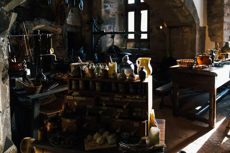 Large Group Of Objects Indoors  Shelf No People Container Still Life Bottle Business Choice Abundance Table Arrangement Variation Workshop Stack Sunlight Day Food And Drink Domestic Room Wood - Material Kitchen Kitchen Utensil Medieval Dated