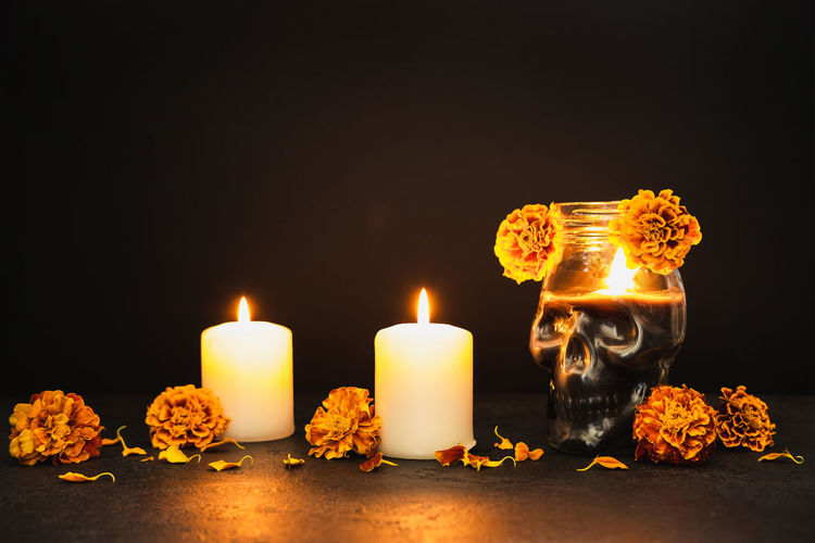Close-up of illuminated candles on table against black background