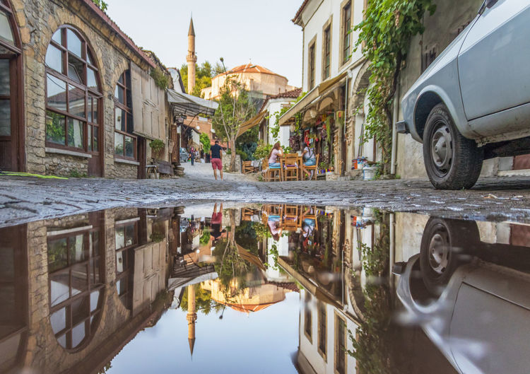 Reflection of mosque in puddle on street