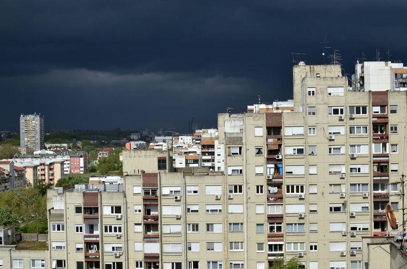 Stormy dark blue sky above a quarter of residential buildings