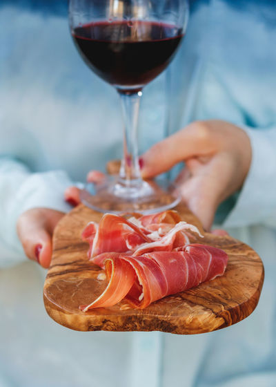 Close-up of wine glass and prosciutto on wooden serving board