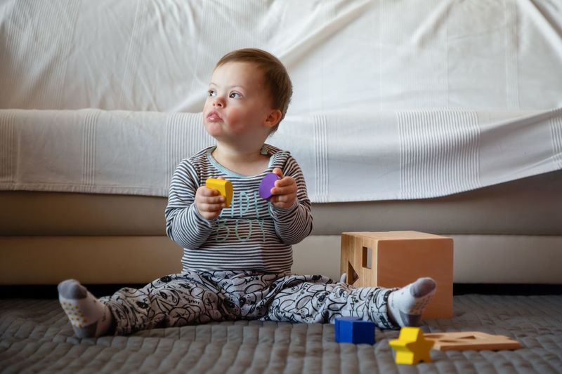 Babyboy Bed Casual Clothing Child Childhood Cute Domestic Room Down Syndrome Full Length Furniture Home Interior Indoors  Innocence Lifestyles Males  Men Mental Health  One Person Playing Real People Sitting Toy