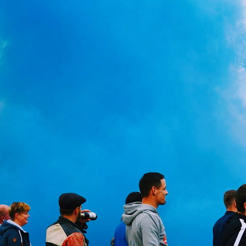 Rear view of people standing against blue sky