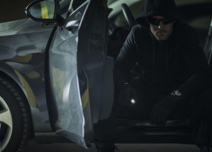 Portrait of burglar sitting in car