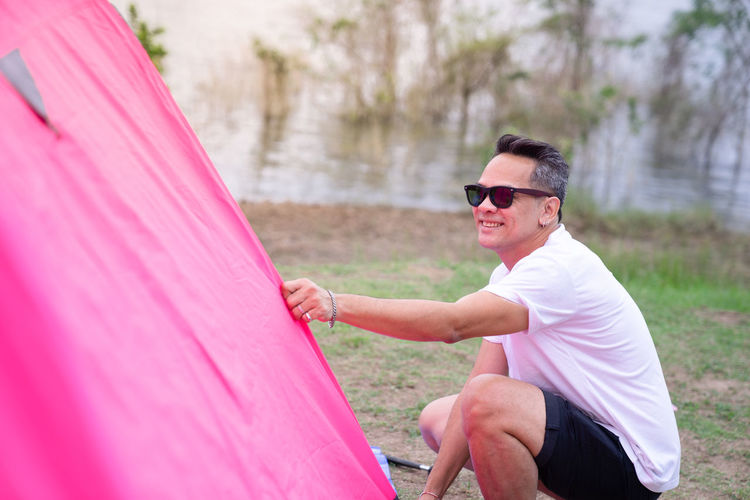 One Person Sunglasses Fashion Real People Glasses Day Leisure Activity Casual Clothing Three Quarter Length Lifestyles Side View Pink Color Adult Young Adult Young Men Men Focus On Foreground Holding Outdoors