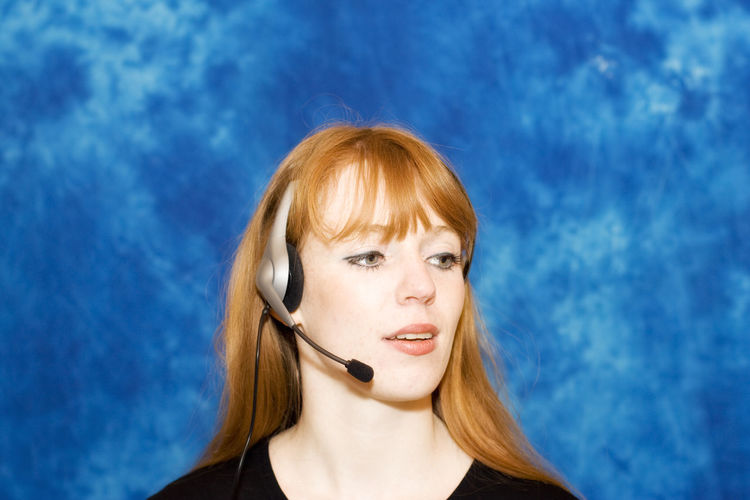 Young businesswoman using headset - concentrated Beautiful Woman Businesswoman Call Center Close-up Communication Connection Head And Shoulders Headset Headshot Occupation One Woman Only One Young Woman Only Portrait Real People Reception Red Hair Service Talking Technology Wireless Technology Woman Working Young Young Adult Young Women
