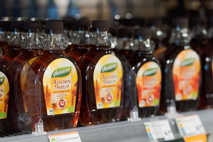 Glass of bottles on shelf at market stall