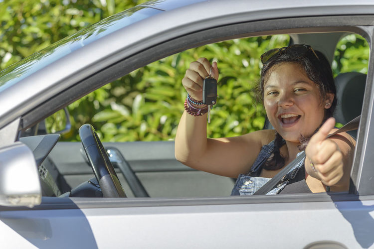 Portrait of happy woman holding key while gesturing in car
