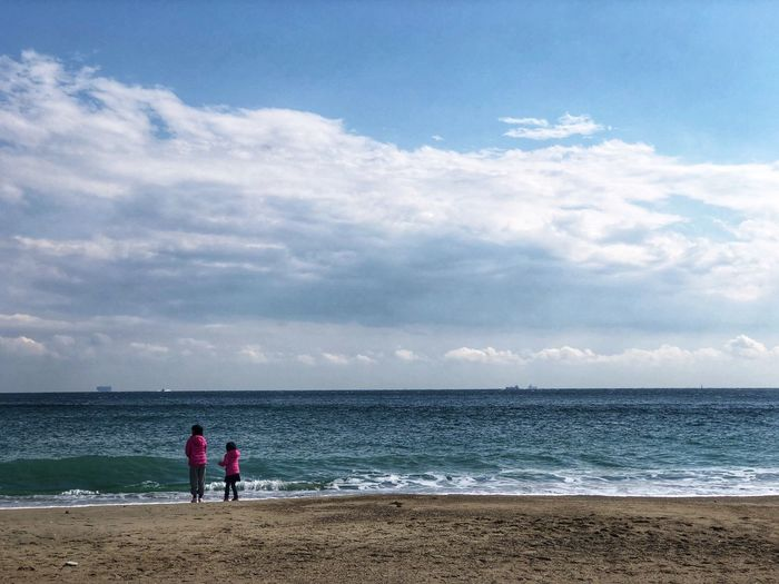 Rear view of sisters standing at beach against cloudy sky