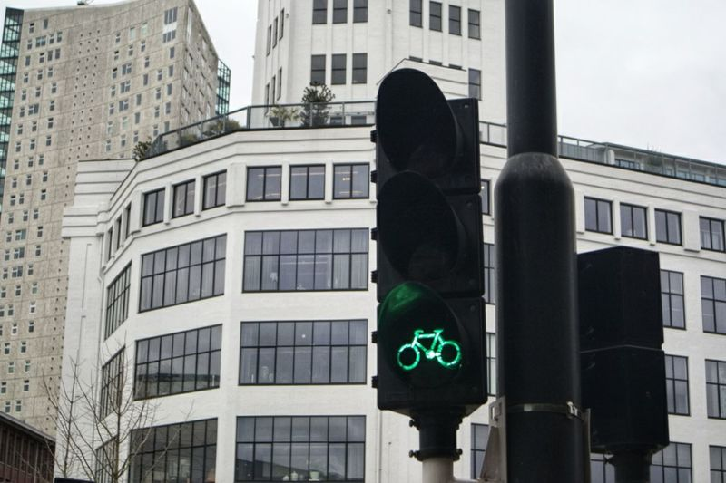 Low angle view of road signal against buildings in city