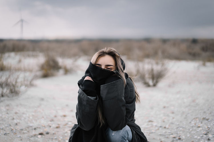 Portrait of woman standing on sand on the beach during winter