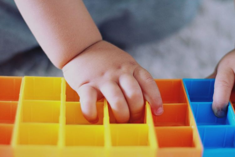 Close-up of boy baby hand playing with toy
