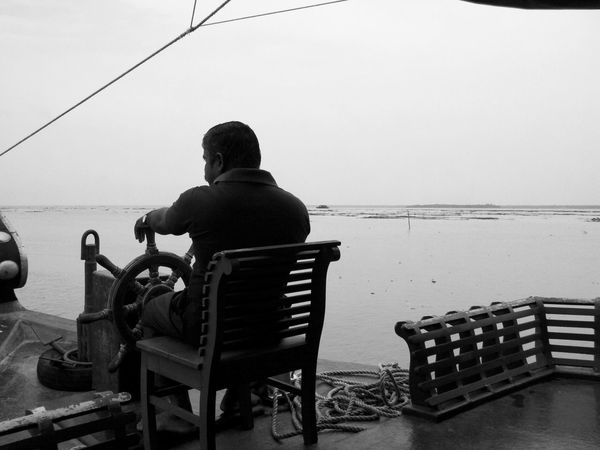 Sea One Man Only Rear View One Person Being The Man Only Men Chair Sitting Captain Horizon Over Water Vacations Relaxation Adults Only Men Water Day Adult Steering Wheel Ship Steering The Ship Boating Helm Vembanad Lake Kerala Kerala Backwaters India