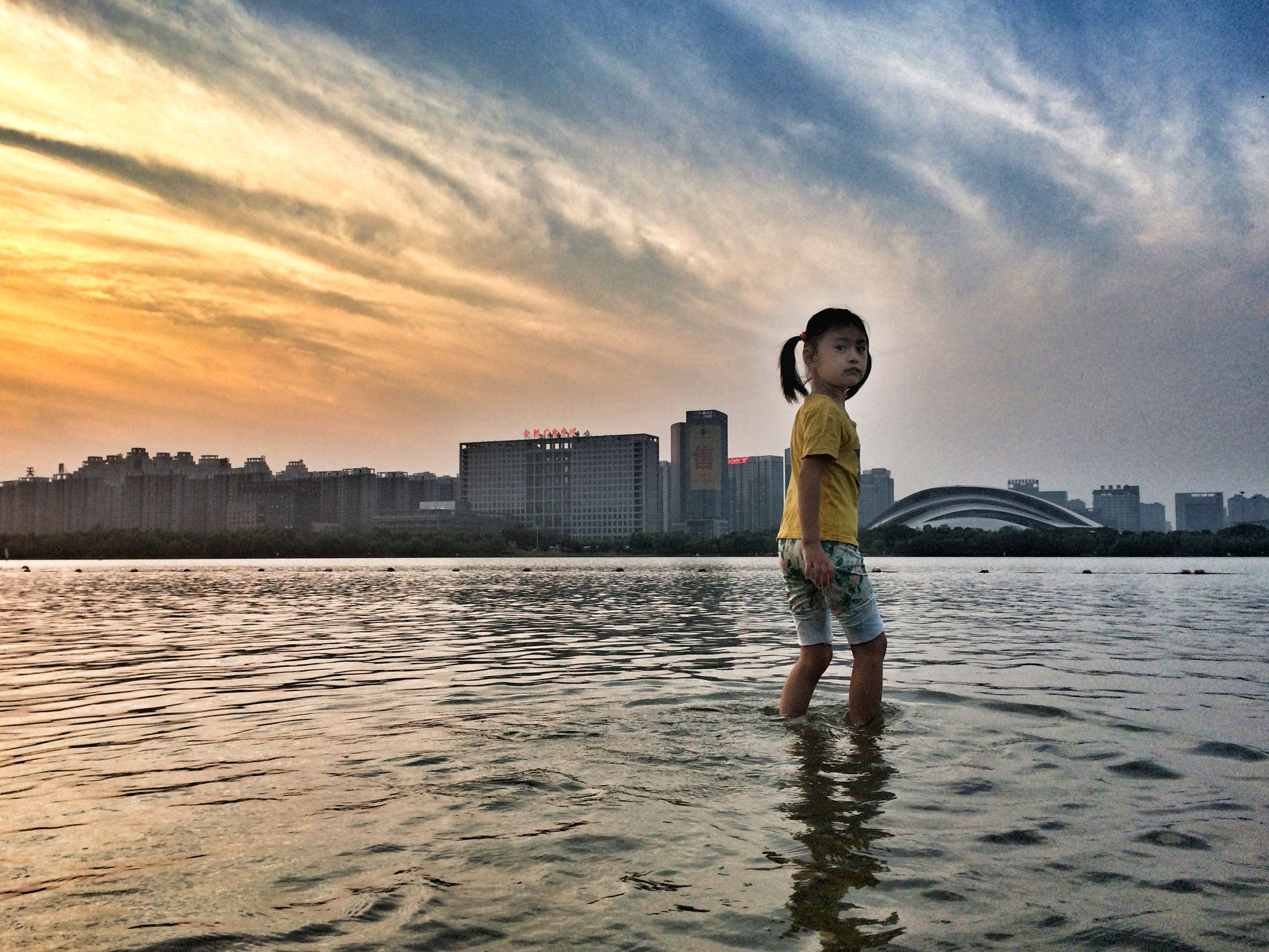 water, building exterior, architecture, sky, built structure, sunset, city, full length, lifestyles, sea, leisure activity, standing, cloud - sky, city life, cityscape, waterfront, rear view, men